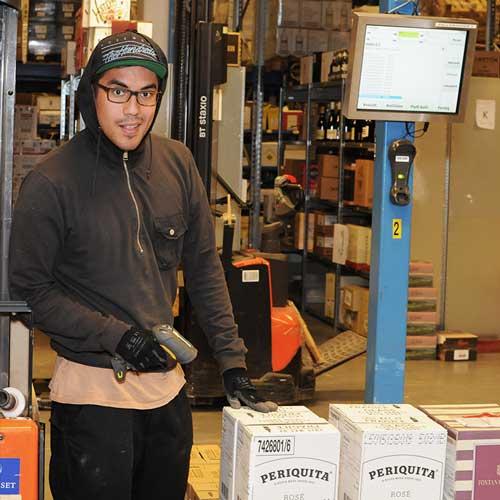 En mann som skanner en eske med vin på et lager