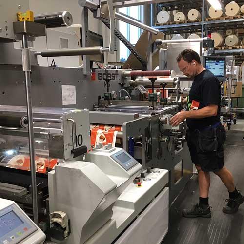 Trykkpresse og en person som jobber med å trykke etiketter