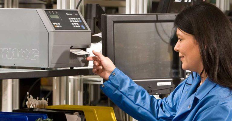 En dame som printer ut en etikett fra en printer