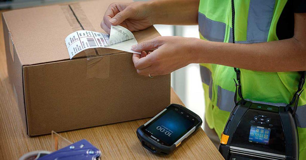 En person som løsner en etikett ved siden av en eske og en håndterminal