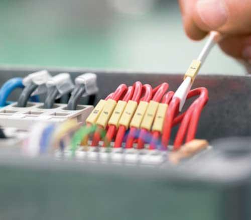 En hånd som jobber med ledninger