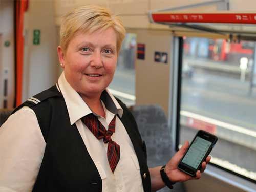 Dame som holder en telefon inne på ett tog