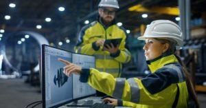 to industriarbeidere foran pcskjermer og med nettbrett