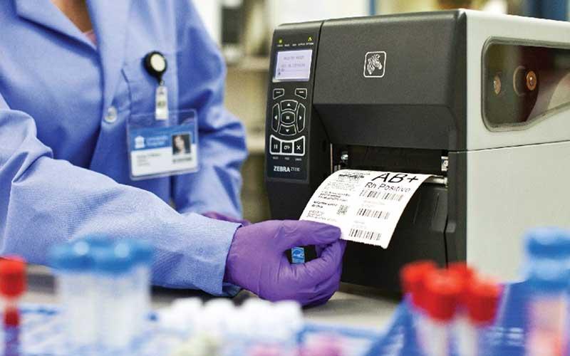 helsepersonell tar ut en etikett fra en printer på en sykehuslab