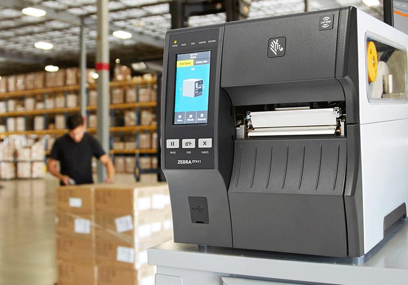 printer i forgrunn på et lager og en lagermedarbeider i bakgrunn