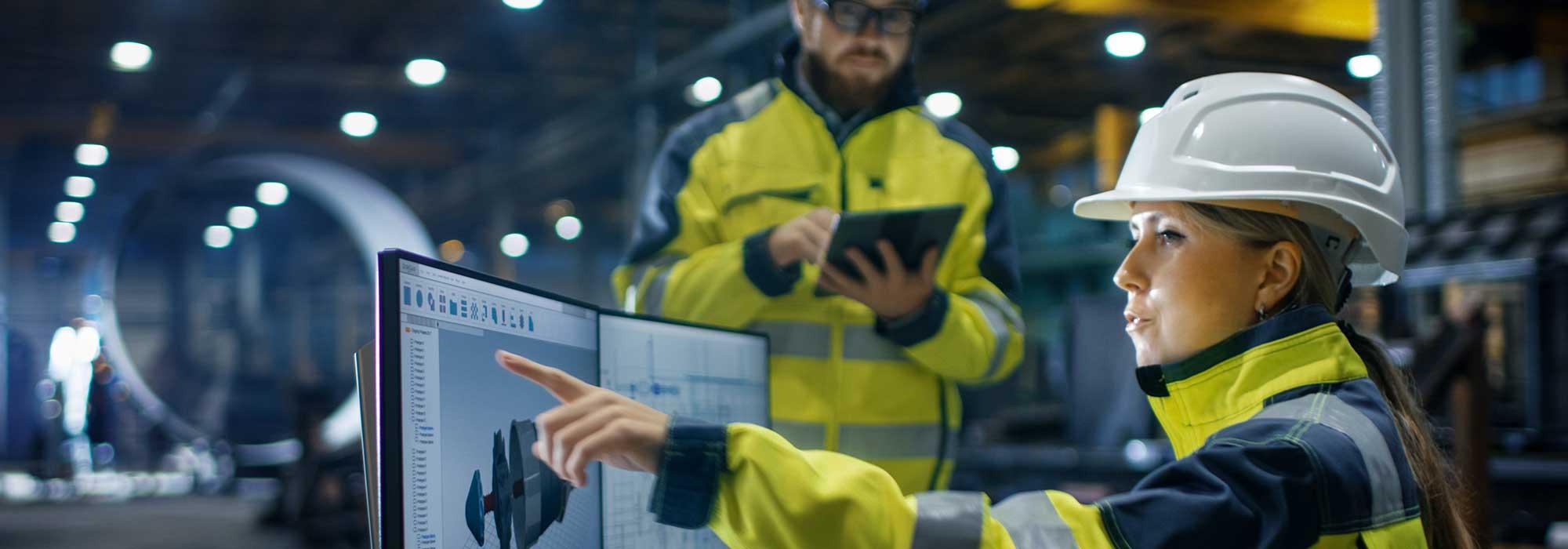 to industriarbeidere foran pc og med en laptop